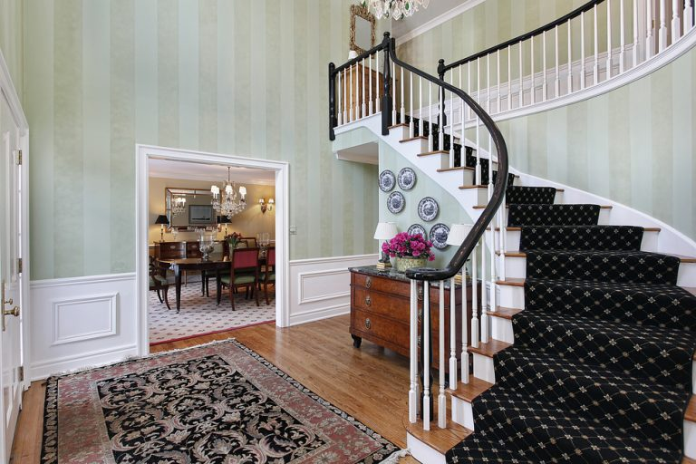 Picture of a foyer with carpeted stairway with a view into the dinning room at our estate sale in Jacksonville, FL