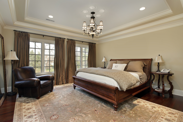 Picture of a luxury bedroom with a tray ceiling and two full windows that expand the one wall in Jacksonville, FL